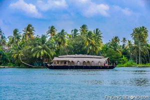 Passing a larger Kerala houseboat. Must See Places in Kerala - Kerala Backwaters.