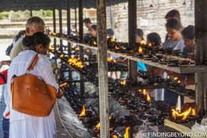 Candle lighting representing the light of Buddha's teachings. Top 5 Things to do in Kandy City in One Day.