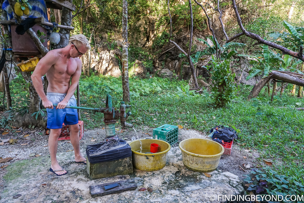 Using the water pump to take an El Nido camping shower at Papaya Beach