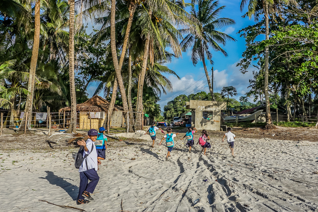 Kids waving at Alimanguan Beach on Long Beach San Vicente Palawan