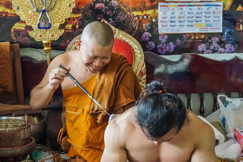 man getting sak yant tattoo in chiang mai
